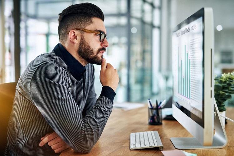 man studying computer screen